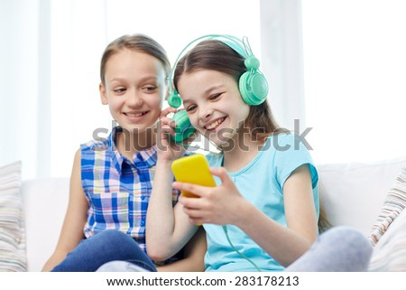 people, children, technology, friends and friendship concept - happy little girls with smartphone and earphones sitting on sofa and listening to music at home - stock photo