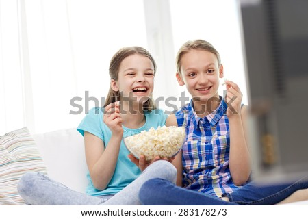 people, children, television, friends and friendship concept - two happy little girls watching comedy movie on tv and eating popcorn at home - stock photo