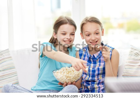 people, children, television, friends and friendship concept - two happy little girls watching tv and eating popcorn at home - stock photo