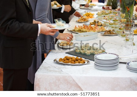 People choosing food from buffet during a wedding ceremony - stock photo