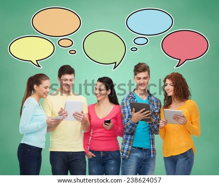 people, communication, school and technology concept - smiling friends with smartphones and tablet pc computers over green board background with text bubbles - stock photo