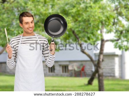people, cooking and culinary concept - happy man or cook in apron with frying pan and wooden spoon over summer garden and house background - stock photo