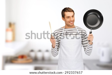 people, cooking and culinary concept - happy man or cook in apron with frying pan and wooden spoon over home kitchen background - stock photo