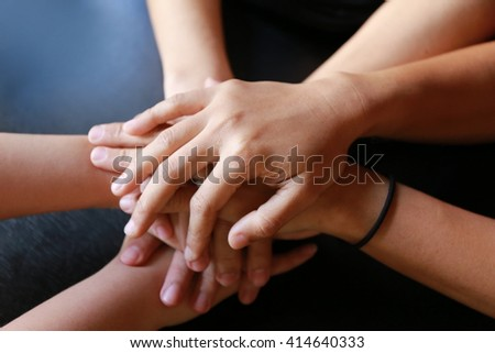 people, cooperation and team work concept - close up of creative team sitting at table and holding hands on top of each,  teamwork hand group - stock photo