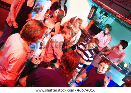 People dancing in a club near the DJ booth where two Dee Jays are playing - stock photo