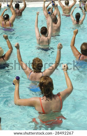 People doing aerobic in a swimming pool - stock photo