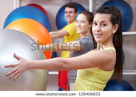 People doing exercise with balls in sport club - stock photo