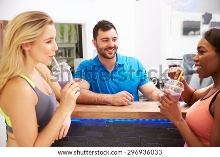 People drinking protein shakes at the fitness bar in a gym - stock photo