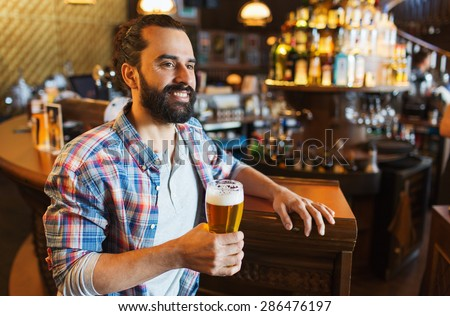 people, drinks, alcohol and leisure concept - happy young man drinking beer at bar or pub - stock photo
