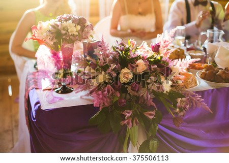 people eating sitting at the table, white and purple flowers, wedding accessories, wedding preparation, decorated wedding table with flowers, wedding flowers, wedding bouquet, food on the table, eat - stock photo