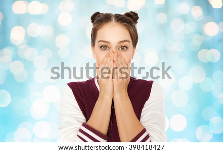 people, emotion, expression and teens concept - scared or confused teenage girl over blue holidays lights background - stock photo