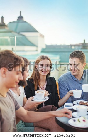 people enjoying coffee together (focus on woman's eyes) - stock photo