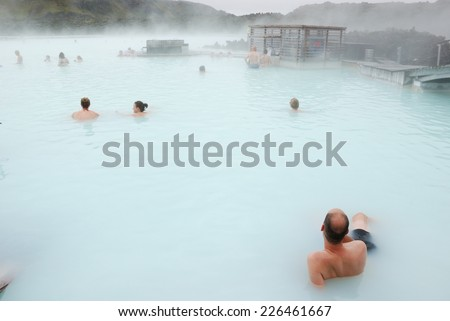 People enjoying hot bath in blue lagoon - stock photo