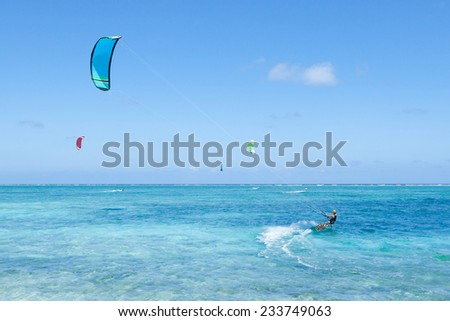 People enjoying kitesurfing on clear blue tropical water, Kume Island, Okinawa, Japan - stock photo