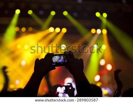 People enjoying rock concert and taking photos with cell phone at music festival - stock photo