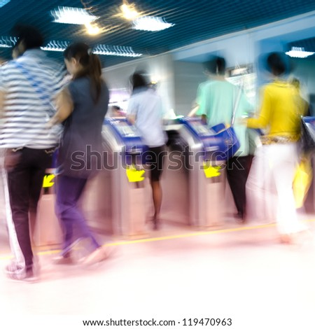 people enter or check out subway station, motion blurred - stock photo