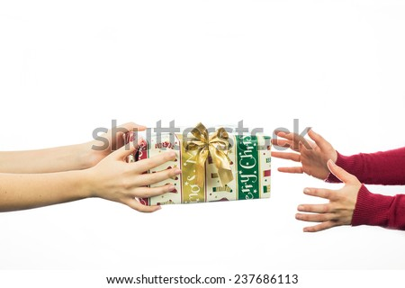 People exchanging Christmas presents. Close up on female hands exchanging gifts isolated on white with copy space - stock photo