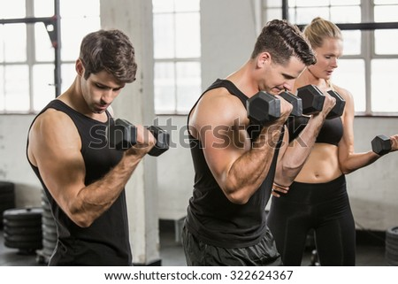 People exercising with dumbbell at the gym - stock photo