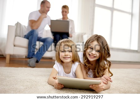 people, family, technology and children concept - happy little girls playing with tablet pc computer at home - stock photo