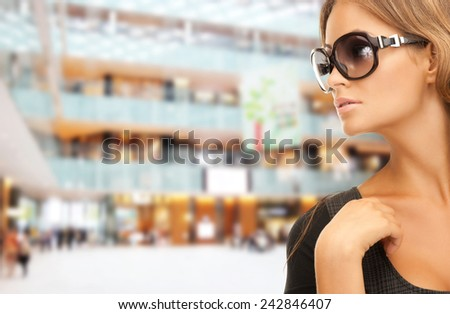 people, fashion, shopping, eyewear and style concept - beautiful woman in shades over mall background - stock photo