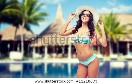 people, fashion, summer vacation and travel concept - happy young woman in bikini swimsuit, sunglasses and sun hat over swimming pool, bungalow and palm trees at hotel resort background - stock photo