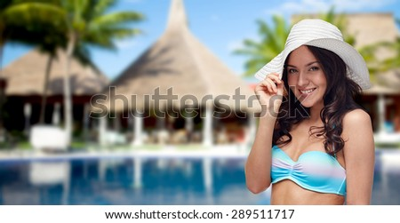 people, fashion, summer vacation and travel concept - happy young woman in bikini swimsuit and sun hat over swimming pool, bungalow and palm trees at hotel resort background - stock photo