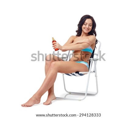 people, fashion, swimwear, summer and beach concept - happy young woman in bikini swimsuit sunbathing on folding chair and applying sunscreen to her skin - stock photo
