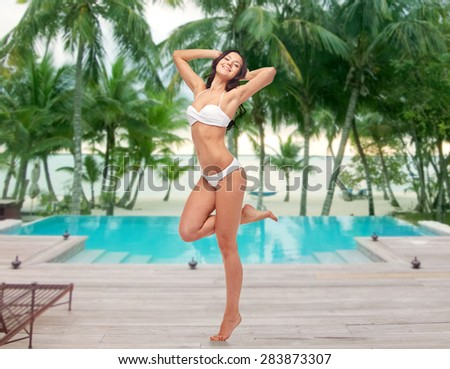 people, fashion, swimwear, summer and beach concept - happy young woman posing in white bikini swimsuit with raised hands and standing on one leg over swimming pool at beach resort - stock photo