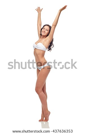 people, fashion, swimwear, summer and beach concept - happy young woman posing in white bikini swimsuit dancing with raised hands - stock photo