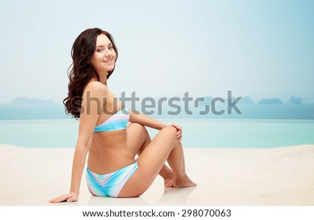 people, fashion, swimwear, summer and beach concept - happy young woman sunbathing in bikini swimsuit over infinity edge pool at hotel resort background - stock photo