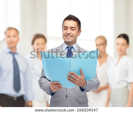 people, finances and work concept - happy smiling businessman in suit holding open folder over business team in office background - stock photo