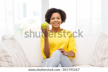 people, food, healthy eating and dental care concept - happy african american young woman with green apple sitting on sofa at home - stock photo