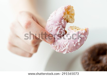 people, food, junk-food and eating concept - close up of female hand holding bitten glazed donut - stock photo