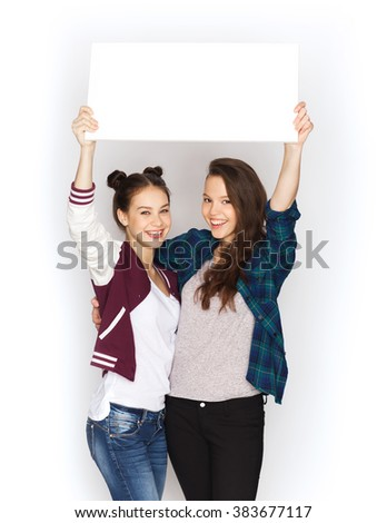 people, friends, teens and friendship concept - happy smiling pretty teenage girls holding and showing white blank board - stock photo