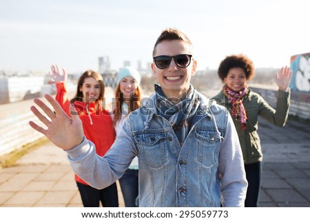 people, friendship and international concept - happy african american young man or teenage boy in front of his friends waving hands on city street - stock photo