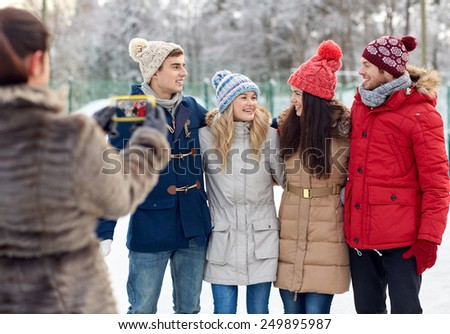 people, friendship, winter, technology and leisure concept - happy friends taking picture with smartphone outdoors - stock photo