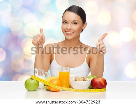 people, gesture and diet concept- happy asian woman with healthy food showing thumbs up over blue lights background - stock photo