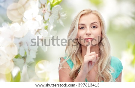 people, gesture and secret concept - beautiful young woman holding finger at her lips over natural spring background - stock photo