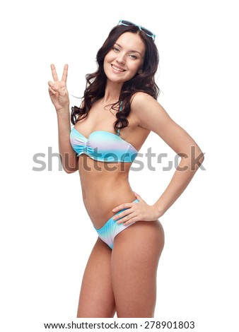 people, gesture, summer, beach and  fashion concept - happy woman in bikini swimsuit showing victory hand sign - stock photo
