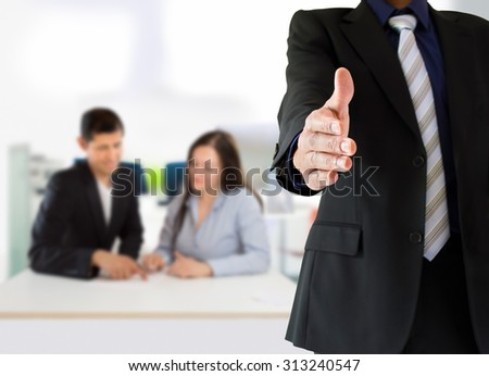 people giving welcoming to the corporate with two persons in the background at the office. The man giving wellcome and the man who is in the meeting is the same person. - stock photo