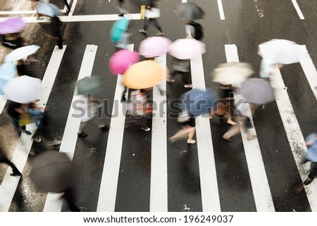 People go across the street in the rain. - stock photo