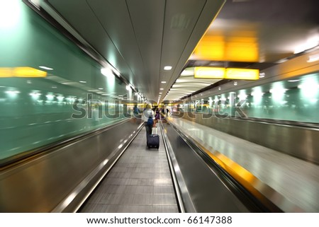 people go into long, green corridor for boarding at airplane - stock photo
