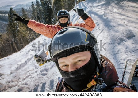 People group have fun on ski snow at winter season on mountain. Two snowboarders taking a self portrait with mobile phone. Tourists having fun while skiing.  - stock photo
