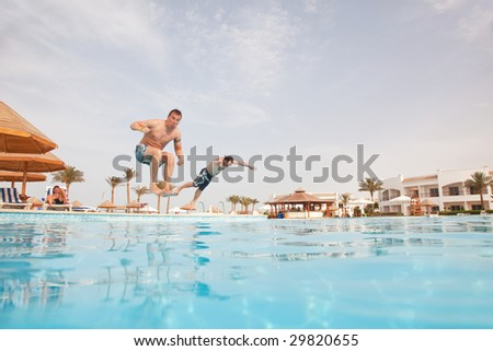 People group resting near swimming pool. Low angle view from the swimming pool. - stock photo