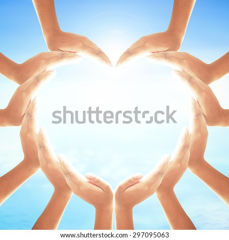 People hands for heart shape over blurred ocean, blue sky and cloud background. World Mental Health Day, Dignity, Insurance, Love, Unity, Investment, Pray, Valentine, Thanksgiving, Christmas concept. - stock photo