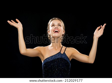 people, happiness, holidays and glamour concept - laughing woman rising hands and looking up over black background - stock photo