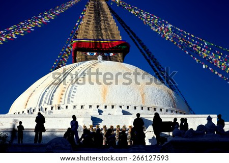 People have a rest beneath the shadow of the great buddhist stupa. Bodnath, Kathmandu, Nepal - stock photo