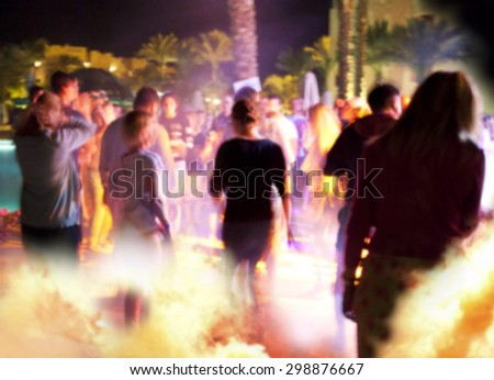 People have fun at night on a beach. Blurry. - stock photo