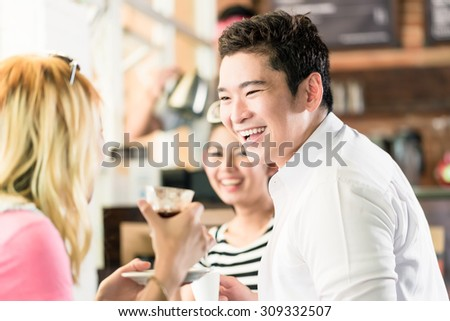 People having coffee and fun in Asian cafe drinking espresso - stock photo