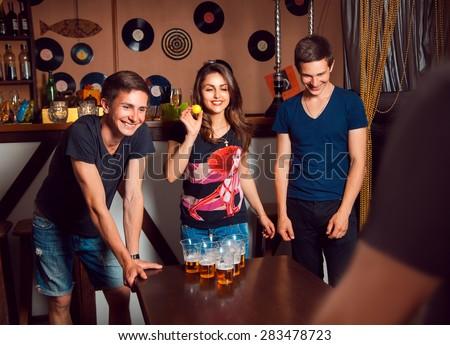 People having fun playing a beerpong at bar. horizontal photo - stock photo